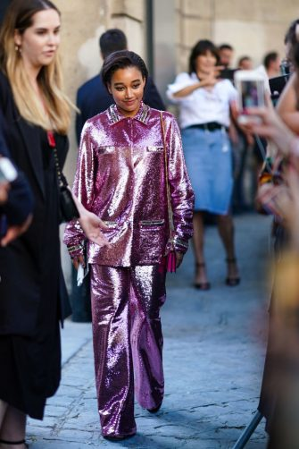 PARIS, FRANCE - JULY 03: Amandla Stenberg wears a shiny glitter  purple/pink outfit, made of a jacket and flare pants, outside Valentino, during Paris Fashion Week -Haute Couture Fall/Winter 2019/2020, on July 03, 2019 in Paris, France. (Photo by Edward Berthelot/Getty Images)