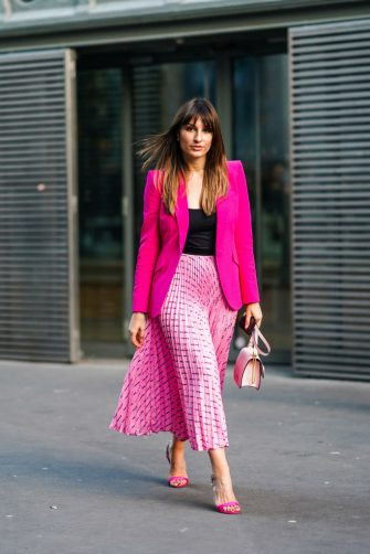 PARIS, FRANCE - JANUARY 20: Carlotta Rubaltelli wears earrings, a necklace, a black top, a neon-pink jacket, a Miu Miu pink pleated skirt, a white Valentino bag, rhinestone embellished neon-pink heeled sandals, outside Ralph & Russo, during Paris Fashion Week - Haute Couture Spring/Summer 2020, on January 20, 2020 in Paris, France. (Photo by Edward Berthelot/Getty Images )