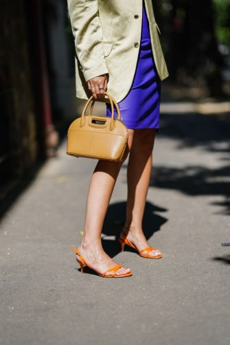 PARIS, FRANCE - JULY 07: Gabriella Berdugo wears a brown leather bag from Maje, a purple leather skirt, orange shoes from Guessepe Zanoti, on July 07, 2020 in Paris, France. (Photo by Edward Berthelot/Getty Images)