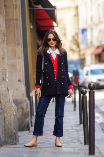 PARIS, FRANCE - MARCH 19: Therese Hellström wears Ray-Ban sunglasses, a white shirt with Peter Pan collar, a navy dark blue oversized military wool jacket with golden buttons, a red wool cardigan with golden heart-shaped buttons, a brown leather Hermes bag, blue denim jeans, beige quilted shoes, on March 19, 2021 in Paris, France. (Photo by Edward Berthelot/Getty Images)