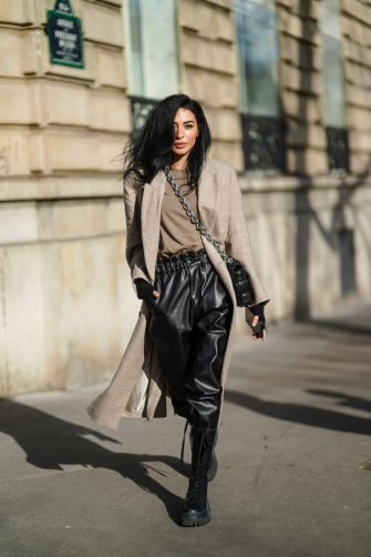 """PARIS, FRANCE - FEBRUARY 23: Damy Aghlam aka """"Gamine de Paris"""" wears a beige long wool coat, a brown t-shirt, black leather pants, a black woven leather Bottega Veneta bag with a metallic chain, black leather knee high combat / military boots with shoelace, on February 23, 2021 in Paris, France. (Photo by Edward Berthelot/Getty Images)"""
