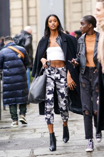 PARIS, FRANCE - FEBRUARY 29: A model wears a black long coat, a white cropped top, cropped military camouflage printed pattern gray pants, black leather pointy shoes, a leather bag, outside Altuzarra, during Paris Fashion Week - Womenswear Fall/Winter 2020/2021, on February 29, 2020 in Paris, France. (Photo by Edward Berthelot/Getty Images)