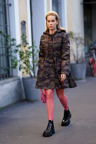 MILAN, ITALY - FEBRUARY 21: Sira Pevida wears a headband, a military camouflage khaki long puffer coat, a pink bag, red tights, black leather shoes, outside Tod's, during Milan Fashion Week Fall/Winter 2020-2021 on February 21, 2020 in Milan, Italy. (Photo by Edward Berthelot/Getty Images)
