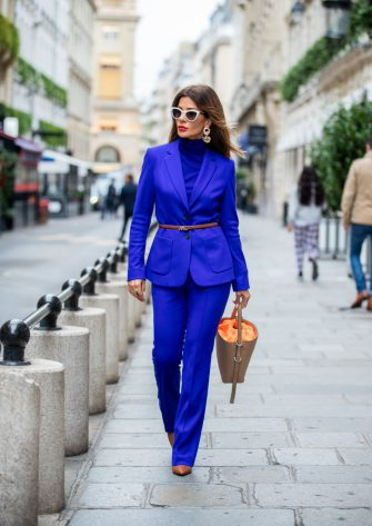 PARIS, FRANCE - SEPTEMBER 26: Füsun Lindner is seen wearing total look Marc Cain: blue knit, suit, brown bag and shoes during Paris Fashion Week Womenswear Spring Summer 2020 on September 26, 2019 in Paris, France. (Photo by Christian Vierig/Getty Images)