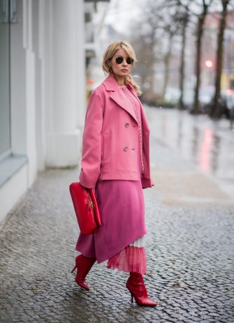 BERLIN, GERMANY - JANUARY 18: Gitta Banko wearing a total Agnona look containing a pink-colored caban-style cashmere jacket, pink caftan, light-pink cashmere sweater, ivory and pink colored pleated skirt, red leather clutch, long gold earings with coral drops and a gold oversize necklace by Georg Hornemann, red ankle sock boots by Fendi and gold Round Metal sunglasses by Ray Ban is seen during the Berlin Fashion Week January 2018 on January 18, 2018 in Berlin, Germany. (Photo by Christian Vierig/Getty Images)