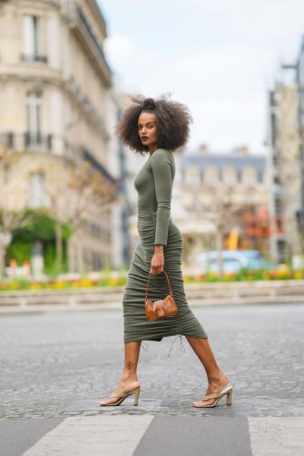 PARIS, FRANCE - APRIL 29: Alicia Aylies wears a green midi dress, a brown leather bag with crocodile pattern, beige sandals shoes, on April 29, 2021 in Paris, France. (Photo by Edward Berthelot/Getty Images)
