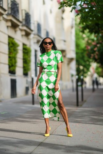 PARIS, FRANCE - MAY 11: Emilie Joseph @in_fashionwetrust wears a green and white printed / checked crepe midi dress with slit and high collar by Rowen Rose, a golden chain belt, yellow leather pointy stilettos with high heels , on May 11, 2021 in Paris, France. (Photo by Edward Berthelot/Getty Images)