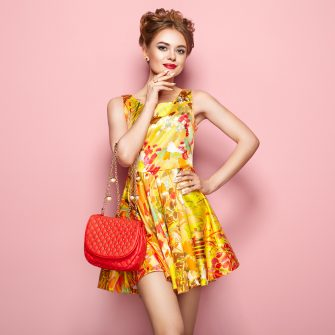 Portrait of Fashion Young woman in Floral Dress. Female Model in Stylish Spring Summer Outfit. Girl Posing on a Pink Background. Stylish Hairstyle. Blonde Lady with Red Handbag