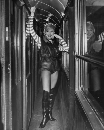 English actress and dancer Joyce Blair (1932 - 2006), sister of Lionel Blair, leaves Victoria Station in London by train for Worthing, wearing her costume for the pantomime 'Dick Whittington', 20th December 1963. She will be appearing in the production at Worthing. (Photo by Keystone/Hulton Archive/Getty Images)