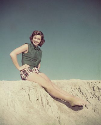 (Original Caption) Sun Worshipper: MGM star Esther William wears these gay plaid shorts topped by a vest of forest green linen for a day at the beach. Miss William is currently in Jupiter's Darling in which she stars with Howard Keel and Marge and Gower Champion. It is directed by George Sidney and produced by George Wells.