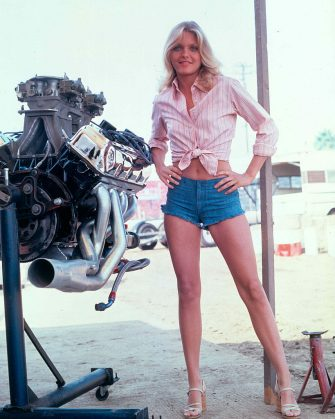 Full length portrait of Michelle Pfeiffer, US actress, wearing a pink blouse, tied at the waist and a pair of denim hot pants, posing beside an engine mounted on an engine jig in a publicity portrait issued for the US television series, 'BAD Cats', USA, 1980.  (Photo by Silver Screen Collection/Getty Images)