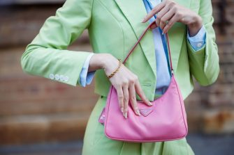 SYDNEY, AUSTRALIA - JUNE 02:(EDITORS NOTE: Image was created in camera using a reflective surface.) Jolie Nguyen, bag detail, wearing Nudie Eye green cropped suit, Prada pink bag and Bottega Veneta shoes at Afterpay Australian Fashion Week 2021 on June 02, 2021 in Sydney, Australia. (Photo by Hanna Lassen/Getty Images)