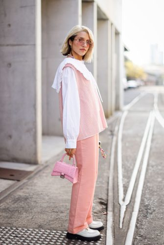 SYDNEY, AUSTRALIA - JUNE 01: (EDITORS NOTE: Image was created in camera using a reflective surface.) Maxine Wylde wearing Blanca Studio shirt, Frankie Shop vest, Onarins pants, Gucci shoes and sunglasses and Balenciaga pink leather bag at Afterpay Australian Fashion Week 2021 on June 01, 2021 in Sydney, Australia. (Photo by Hanna Lassen/Getty Images)
