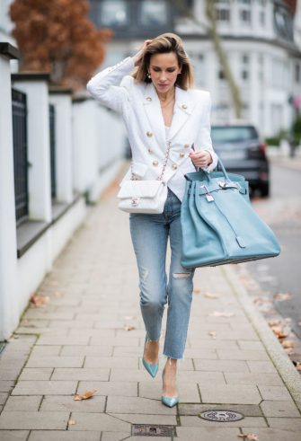 DUESSELDORF, GERMANY - DECEMBER 10: Alexandra Lapp is seen wearing white double-breasted Balmain blazer with golden buttons, silk top, white Chanel bag, light blue turquois oversized Hermès Birkin Bag, light blue ripped Celine denim jeans, Prada pumps, Dior earrings on December 10, 2019 in Duesseldorf, Germany. (Photo by Christian Vierig/Getty Images)