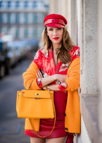 DUESSELDORF, GERMANY - MAY 06: Alexandra Lapp wearing the Evangelista knitted cardigan by Ganni in turmeric orange, Hawaiian multicolored silk kimono with all-over print by Jadicted, ruffled mini skirt in red leather by Magda Butrym, a Hermes birkin 30 bag in orange, Gianvito Rossi red patent pumps and gold mirrored Thom Browne sunglasses in red on May 6, 2018 in Duesseldorf, Germany. (Photo by Christian Vierig/Getty Images)