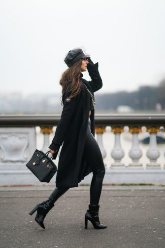 PARIS, FRANCE - FEBRUARY 08: Carina Zavline wears a black leather beret hat with a veil from Dior, a black wool cropped bare-belly turtleneck pullover from Nu-In Fashion, a golden long chain necklace from Chanel, a black long coat from Kazai, a black leather Hermes Birkin bag, black latex shiny leggings / pants from Saint-Laurent YSL, black leather high heeled pointy boots from Saint-Laurent YSL, on February 08, 2021 in Paris, France. (Photo by Edward Berthelot/Getty Images)
