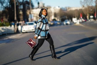 """PARIS, FRANCE - JANUARY 09: Carrole Sagba aka """"Linaose"""" wears a blue and white checked wool jacket from Zara, a purple / burgundy leather Hermes Birkin bag, black leggings/pants from Acne Studios, black pointy high heeled knee-high leather boots with printed crocodile patterns from Dear Frances, on January 09, 2021 in Paris, France. (Photo by Edward Berthelot/Getty Images)"""