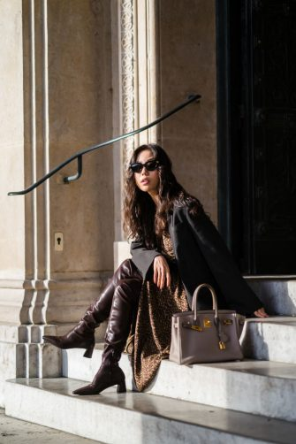 PARIS, FRANCE - DECEMBER 20: Fashion blogger Xiayan wears sunglasses from Bottega Veneta, a black oversized blazer jacket from Les Coyotes de Paris, a brown gathered leopard print long dress from Les Coyotes de Paris, brown leather pointy boots from Charles & Keith, a Hermes Birkin beige leather bag, a golden necklace, on December 20, 2020 in Paris, France. (Photo by Edward Berthelot/Getty Images)