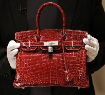 A employee holds a 129,000 USD crocodile Hermes Birkin Bag for the press to see during a private opening for the new Hermes store on Wall Street in New York 21 June 2007. The store which is located at 15 Broad Steet is across the street from the New York Stock Exchange. The store is one of several luxury shops opening near Ground Zero as part of a revitalization project in the area.  AFP PHOTO/ TIMOTHY A.  CLARY        (Photo credit should read TIMOTHY A. CLARY/AFP via Getty Images)