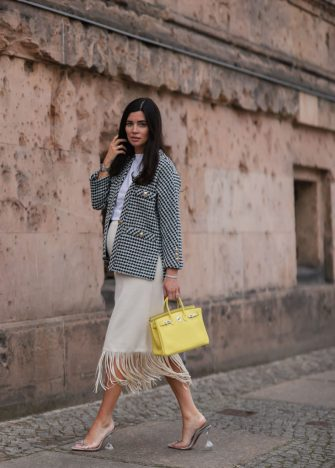 BERLIN, GERMANY - JUNE 01: Leo Mathild wearing black and white chequered Maje jacket, beige Sandro fringe skirt, clear Amina Muaddi heels and yellow Hermes Birkin 25 leather bag on June 01, 2021 in Berlin, Germany. (Photo by Jeremy Moeller/Getty Images)