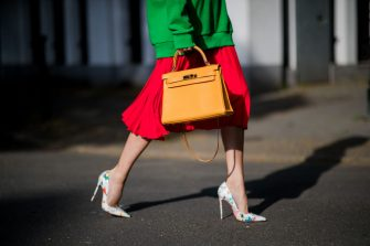 DUESSELDORF, GERMANY - MAY 03: Alexandra Lapp wearing a green tiger print Gucci logo hoodie, a red pleated skirt by SET, a Hermes Birkin 30 bag in orange, Pigalle Follies pumps by Christian Louboutin and green mirrored Ray Ban sunglasses on May 3, 2018 in Duesseldorf, Germany. (Photo by Christian Vierig/Getty Images)