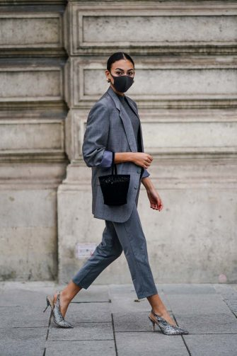 PARIS, FRANCE - OCTOBER 06: A Maria Decremps wears a black face mask, earrings, a gray oversized blazer jacket, a gray wool pullover, cropped pants, snake pattern printed pointy shoes, a bag, outside Louis Vuitton, during Paris Fashion Week - Womenswear Spring Summer 2021, on October 06, 2020 in Paris, France. (Photo by Edward Berthelot/Getty Images)