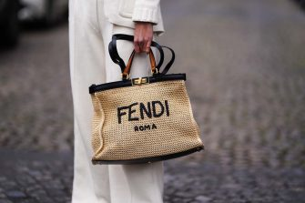 PARIS, FRANCE - MARCH 12: Natalia Verza @mascarada.paris wears a Fendi total look, a Fendi logo beige straw tote bag / beach bag, white flare suit pants from Fendi, on March 12, 2021 in Paris, France. (Photo by Edward Berthelot/Getty Images)