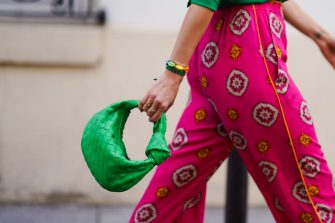 PARIS, FRANCE - MARCH 26: Alexandra Pereira wears colored bracelets shaped as sea shells, a green woven leather bag from Bottega Veneta, bold pink flare pants with printed patterns, on March 26, 2021 in Paris, France. (Photo by Edward Berthelot/Getty Images)