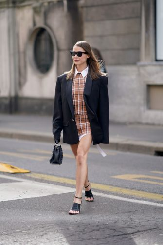 MILAN, ITALY - FEBRUARY 21: Sophia Roe wears sunglasses, an oversized black blazer jacket, a brown checked top and short skirt, a white shirt, a black bag, black leather shoes, outside Sportmax, during Milan Fashion Week Fall/Winter 2020-2021 on February 21, 2020 in Milan, Italy. (Photo by Edward Berthelot/Getty Images)