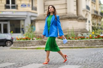 PARIS, FRANCE - APRIL 28: Ketevan Giorgadze @katie.one wears a midi green dress featuring a round neckline, long gathered sleeves from Zara, orange slingback pointed pumps from Asos, an oversized blue blazer jacket from Zara, a beaded handbag in blue from Madame Chatelet, rhinestone-detail earrings from recycled metal with a decorative orange pendant from H&M, on April 28, 2021 in Paris, France. (Photo by Edward Berthelot/Getty Images)