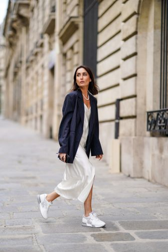 PARIS, FRANCE - JUNE 29: Geraldine Boublil wears a white pearl necklace from Coconut Love, a dark navy blue striped oversized blazer jacket from Gauge 81, a white lustrous silky shiny low-neck dress from Basilika, Hogan white and silver sneakers, on June 29, 2020 in Paris, France. (Photo by Edward Berthelot/Getty Images)