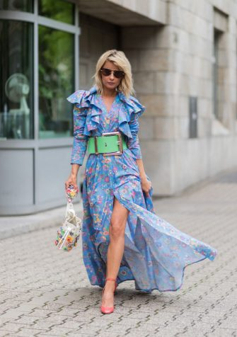 DUESSELDORF, GERMANY - AUGUST 6:  Model and fashion blogger Gitta Banko wearing a floral-patterned dress and a pastel-green oversize waist belt by Marina Hoermanseder, a Kasper Flowers bucket bag made of vegetable tanned leather, salmon-pink patent-leather Tango pumps by Valentino and sunglasses by Miu Miu on August 6, 2017 in Duesseldorf, Germany. (Photo by Christian Vierig/Getty Images)