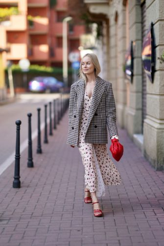MILAN, ITALY - FEBRUARY 21: Thora Valdimars wears a black and white checked pattern oversized blazer jacket, a white floral print low neck dress, a red woven leather Bottega Veneta bag, red shoes, outside Marni, during Milan Fashion Week Fall/Winter 2020-2021 on February 21, 2020 in Milan, Italy. (Photo by Edward Berthelot/Getty Images)