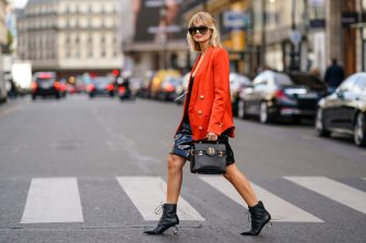 PARIS, FRANCE - SEPTEMBER 27: Xenia Adonts wears sunglasses, a red oversized blazer jacket, a Balmain logo bag, a black dress, black leather boots with metallic heels, outside Balmain, during Paris Fashion Week - Womenswear Spring Summer 2020 on September 27, 2019 in Paris, France. (Photo by Edward Berthelot/Getty Images)