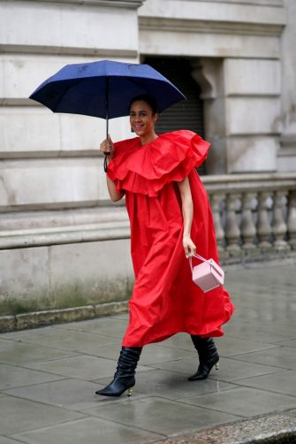 LONDON, ENGLAND - FEBRUARY 16: Zawe Ashton wears a red ruffled dress, a pastel ping bag, black leather pointy boots with small golden heels, during London Fashion Week Fall Winter 2020 on February 16, 2020 in London, England. (Photo by Edward Berthelot/Getty Images)