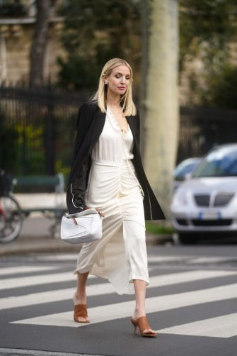 PARIS, FRANCE - MARCH 03: Leonie Hanne wears earrings, a black oversized jacket, a white dress, a white bag, brown pointy shoes, outside Gauchere, during Paris Fashion Week - Womenswear Fall/Winter 2020/2021 on March 03, 2020 in Paris, France. (Photo by Edward Berthelot/Getty Images)