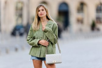 PARIS, FRANCE - JUNE 08: Xenia Adonts wears gold earrings, a green suede oversized vintage jacket, blue denim ripped jeans shorts from Gucci, a white shiny quilted leather Chanel Boy crossbody bag, on June 08, 2021 in Paris, France. (Photo by Edward Berthelot/Getty Images)