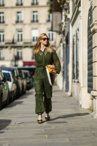 PARIS, FRANCE - JUNE 04: Natalia Verza @mascarada.paris wears sunglasses, a green khaki mesh jumpsuit from Fendi with embroidered logo / monograms, an orange Fendi knit bag, green high heels Fendi shoes with sequins, on June 04, 2021 in Paris, France. (Photo by Edward Berthelot/Getty Images)