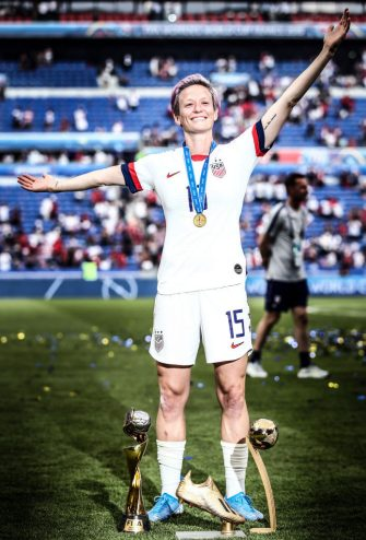 LYON, FRANCE - JULY 07: (EDITORS NOTE: Image has been digitally enhanced.) Megan Rapinoe of the USA celebrates with the FIFA Women's World Cup Trophy, the Golden Boot and The Golden Ball following the 2019 FIFA Women's World Cup France Final match between The United States of America and The Netherlands at Stade de Lyon on July 07, 2019 in Lyon, France. (Photo by Alex Grimm/Getty Images)