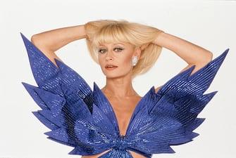 Portrait of Italian showgirl and TV presenter Raffaella Carrà (Raffaella Pelloni) wearing a blue stage costume tied on her breast. 1984. (Photo by Rino Petrosino/Mondadori via Getty Images)