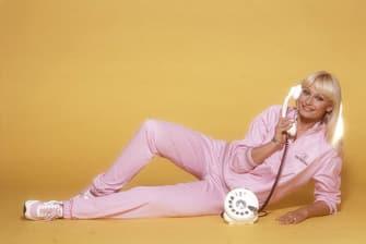 Italian TV presenter, actress, singer and showgirl Raffaella Carrà (Raffaella Maria Roberta Pelloni) lying wearing a pink tracksuit with a receiver in her right hand. 1984. (Photo by Rino Petrosino/Mondadori via Getty Images)