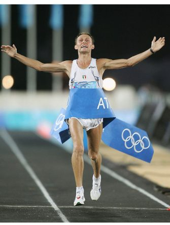 ATHENS - AUGUST 29:  Stefano Baldini of Italy celebrates as he crosses the finish line first to win the gold medal in the men's marathon on August 29, 2004 during the Athens 2004 Summer Olympic Games at Panathinaiko Stadium in Athens, Greece.  (Photo by Clive Mason/Getty Images)