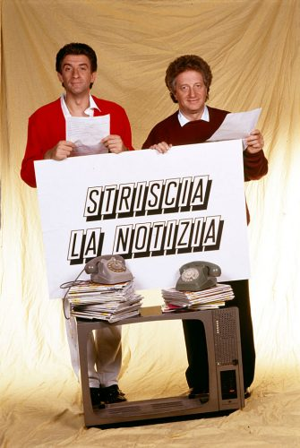 """""""Ezio Greggio and Gianfranco D'Angelo promote the new broadcast by Antonio Ricci, """"""""Striscia la notizia"""""""", meant to be a satirical newscast; the two Italian comedians show a sign reporting the title of the program on a completely emptied television (1988, Segrate, Milan, Italy).  (Photo by Angelo Deligio\Mondadori via Getty Images)"""""""