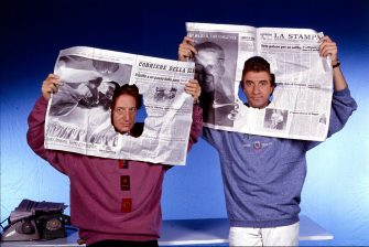"""""""Ezio Greggio and Gianfranco D'Angelo promote the new broadcast by Antonio Ricci, """"""""Striscia la notizia"""""""", meant to be a satirical newscast; Italian actors and comedians look at the camera through holes cut in the browsed newspapers on 1988 in Segrate, Milan, Italy.  (Photo by Angelo Deligio\Mondadori via Getty Images)"""""""