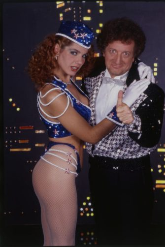 Greek-born Italian showgirl and actress Tinà ¬ Cansino (Photina Lappa) as a sexy fast food girl while posing hugging the comedian Gianfranco D'Angelo on the set of the famous TV comic show 'Drive In' broadcasted by Italia 1. Photo shooting. Milan (Italy), 1984 ( Photo by Angelo Deligio/Mondadori via Getty Images)