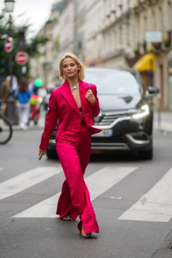 PARIS, FRANCE - JUNE 23: A guest wears a beaded pearl bejeweled necklace, black bras a neon pink / fuchsia lustrous silky / shiny blazer jacket, matching flared slit pants, high heels shoes, outside BLUEMARBLE, during Paris Fashion Week - Menswear Spring/Summer 2022, on June 23, 2021 in Paris, France. (Photo by Edward Berthelot/Getty Images)