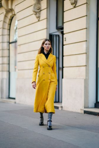 PARIS, FRANCE - SEPTEMBER 10: Natalia Verza wears a black shirt, a yellow long coat from Prada, Prada shoes, on September 10, 2020 in Paris, France. (Photo by Edward Berthelot/Getty Images)