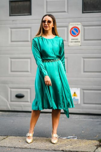 MILAN, ITALY - SEPTEMBER 19: A guest wears sunglasses, a lustrous emerald-green long sleeved dress, a gold-tone chain belt, lustrous beige pointy strappy shoes with bejeweled buckles, outside the Bottega Veneta show during Milan Fashion Week Spring/Summer 2020 on September 19, 2019 in Milan, Italy. (Photo by Edward Berthelot/Getty Images)