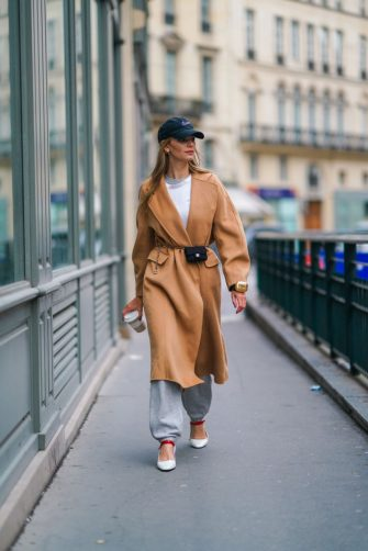 PARIS, FRANCE - FEBRUARY 01: Natalia Verza aka Mascarada wears a black cap from Nike, a white t-shirt, a beige pale brown wool long trench coat, gray sport jogger pants, a golden Prada bracelet bag, a mini black quilted Chanel belt bag, white square toe shoes with red features from Prada, holds a Prada hot drink coffee paper cup, on February 01, 2021 in Paris, France. (Photo by Edward Berthelot/Getty Images)