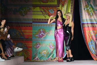 British singer and model Dua Lipa (C) and Italian fashion designer Donatella Versace (R) acknowledge applause following the presentation of Versace's Women's Spring-Summer 2022 collection during the Fashion Week in Milan on September 24, 2021. (Photo by Marco BERTORELLO / AFP) (Photo by MARCO BERTORELLO/AFP via Getty Images)